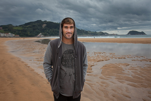 "Aritz Aranburu on the beach of Zarautz. In the background, the famous ""mouse of Getaria"""